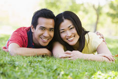 Couple lying outdoors smiling Royalty Free Stock Image