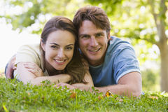 Couple lying outdoors smiling Royalty Free Stock Photography