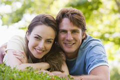 Couple lying outdoors smiling Royalty Free Stock Photo