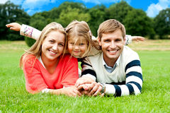 Couple lying in park with their daughter on top Stock Photo