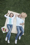 Couple lying on picnic blanket. Stock Photography