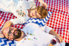 Couple lying on a picnic blanket with glass of wine Stock Image