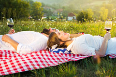 Couple lying on a picnic blanket with glass of wine Royalty Free Stock Image