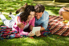 Couple lying on picnic blanket and using digital tablet Stock Image