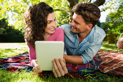 Couple lying on picnic blanket and using digital tablet Stock Images