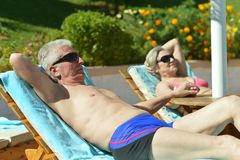 Couple lying by pool Stock Image