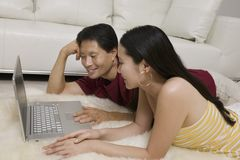 Couple lying on Rug with Laptop Royalty Free Stock Photo