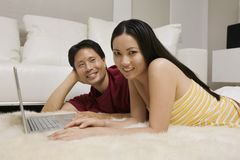 Couple lying on Rug with Laptop portrait ground view Stock Image