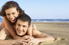 Couple Lying On Sand At Beach Royalty Free Stock Photos