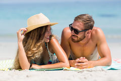Couple lying on sand at beach during sunny day Stock Photography