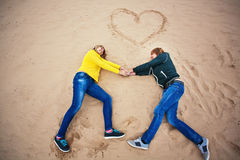 Couple are lying on the sand with a heart Stock Images