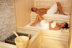 Couple lying in sauna. Wearing towel, relaxing with eyes closed Stock Image