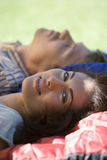 Couple lying on sleeping bags in tent entrance on garden lawn, focus on woman in foreground, smiling, side view, portrait Royalty Free Stock Image
