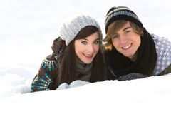 Couple lying in snow Royalty Free Stock Images