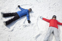Couple Lying On Snow Making Snow Angel Stock Image