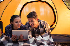 Couple lying in tent and using tablet computer Royalty Free Stock Photo