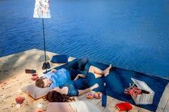Couple  lying on terrace near blue water Stock Photo