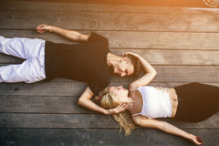 Couple lying together on the hardwood floor Stock Image