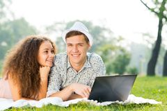 Couple lying together in a park with laptop Stock Image