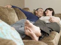 Couple Lying Together On Sofa Stock Image