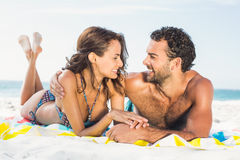 Couple lying on a towel at the beach. On a sunny day Royalty Free Stock Images