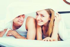 Couple lying under sheet stock image