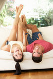 Couple Lying Upside Down On Sofa Royalty Free Stock Images