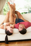 Couple Lying Upside Down On Sofa Stock Photo