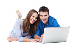 Couple lying and using laptop Stock Images