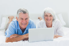 Couple lying and using a laptop in bed Stock Images