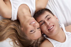 Couple lying on white bed Stock Photos