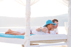 Couple lying on white bed at the sea Royalty Free Stock Images