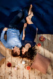 Couple lying on wood floor with pillows and sweets Stock Images