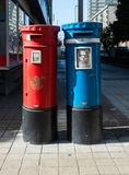 Couple of mail box blu and red on the street stock image