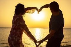 Couple maing heart shape at sunrise. On the beach Royalty Free Stock Photography