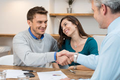 Couple make an investment. Happy young couple shaking hands for a financial agreement Royalty Free Stock Photos
