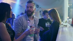 Couple make an order and communicates near bar counter against the background of a company of friends in a club stock video