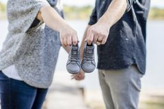 Couple Makes Baby Announcement with a Tiny Pair of Shoes Outside Royalty Free Stock Photos