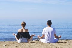 Couple makes meditation in lotus pose on sea / ocean beach, harmony and contemplation. Boy and girl practicing yoga at sea resort. At vacation. Health ife style royalty free stock photos