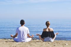 Couple makes meditation in lotus pose on sea / ocean beach, harmony and contemplation. Boy and girl practicing yoga at sea resort. At vacation. Health ife style royalty free stock photo
