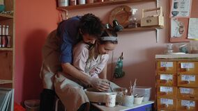 The couple makes pottery out of clay and have fun at the same time.