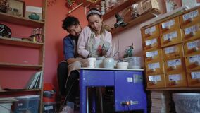 The couple makes pottery out of clay and have fun at the same time