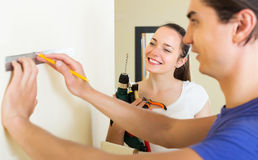 Couple makes repairs at home Stock Images