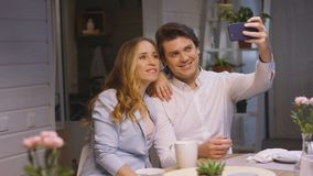 Couple Makes Selfie Sitting at Home Dinner Table. Slow motion closeup happy couple makes selfie sitting at dinner table in cozy atmosphere at home stock video