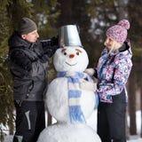 Couple makes snowman Stock Photo