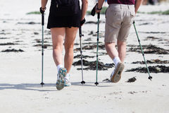 Couple Makes Together Nordic Walking At The Beach Stock Photos