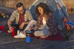 Couple making breakfast while camping. Couple in love on an outdoor camping adventure, preparing a meal at a lake docks and enjoying a beautiful day in nature royalty free stock images