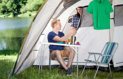 Couple making breakfast in front of tent Stock Photography