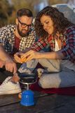Couple making a camping dinner. Couple camping at the lake, cooking eggs for dinner and having fun on an outdoor nature adventure royalty free stock photo