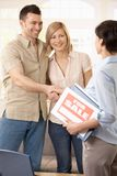 Couple making deal with estate agent. Happy couple making deal with estate agent, shaking hands stock photos